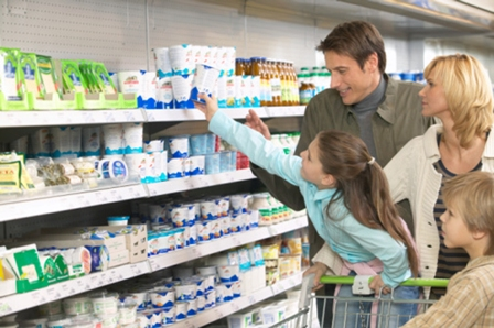 Family shopping in supermarket, girl (8-10) reaching for product on shelf